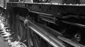 Steam train starting off as wheels spin on track black and white shot 4K. Steam train starts moving on track black and white old style shot but filmed on 4K stock video