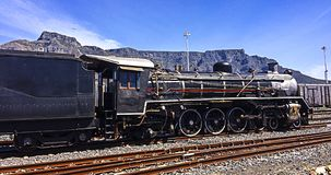 Steam Train with Table Mountain in background. A beautiful old steam train magnificantly posing with table mountain in the background. This was taken at the stock photo