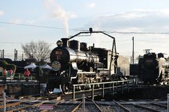 Steam train on turntable tracks. An old steam train puffs out steam as it is turned on a turntable to guide it to the right tracks as visitors to the Umekoji stock photo