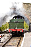 Steam under a bridge. A steam locomotive on a preserved Victorian railway passes under a bridge Stock Photo