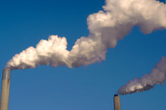 Steam and vapor from smoke stacks chimneys Royalty Free Stock Photos