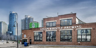 Steam Whistle Brewing. Is a brewery in Toronto. The company produces a premium pilsner lager packaged in distinctive green glass bottles and a non-twist cap Royalty Free Stock Photos