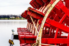 Steamboat Paddle. Red and white paddlewheel showing it's age on a smooth river royalty free stock image