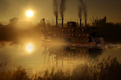 Steamboat at sunrise. Steamboat at the sunrise, close to a bridge on a big river under the mist stock photo