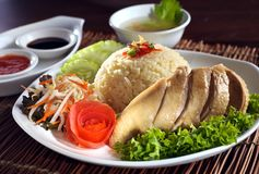 Steamed Asian chicken rice. A plate of steamed chicken rice cooked in asian style with sauce and soup as background Royalty Free Stock Photo