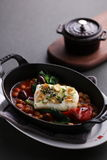 Steamed Atlantic cod saffron braised with bean on black stew Royalty Free Stock Photos