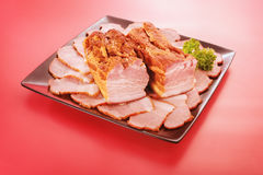 Steamed bacon on a plate. And red background stock photography