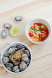Steamed blanched clams in white bowl and spicy dipping sauce Royalty Free Stock Image