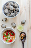 Steamed blanched clams in white bowl and spicy dipping sauce Stock Photo