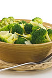 Steamed broccoli. With lemon zest and Parmigiano Reggiano cheese in rustic yellow bowl, vertical format Stock Image