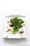 Steamed broccoli rabe. White wine-steamed broccoli rabe with raisins and hazelnuts Stock Image