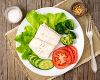 Steamed cod fish. Paleo, keto, fodmap healthy diet with vegetables on white plate on white table, side view. Steamed cod fish. Paleo, keto, fodmap healthy diet stock photos