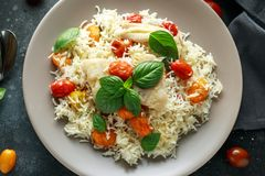 Steamed cod fish with rice and cherry mix tomatoes and basil herbs in a plate royalty free stock image