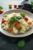 Steamed cod fish with rice and cherry mix tomatoes and basil herbs in a plate stock photo