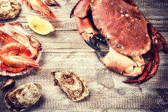 Steamed crab, shrimps and fresh oysters on wooden background Stock Photography