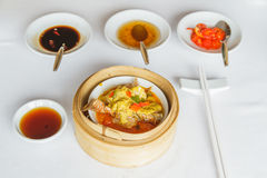 Steamed crab skiff with curry. Dim sum food Steamed crab skiff with curry in bamboo basket at restaurant with soy sauce, sweet sauce, chili sauce and chopsticks Royalty Free Stock Photography