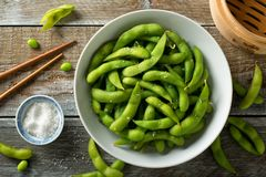 Steamed Edamame with Sea Salt. Fresh steamed edamame sprinkled with sea salt on a rustic tabletop Royalty Free Stock Photos