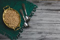 Steamed gold chickpeas in bowl with vintage spoons, tasty vegan food royalty free stock images