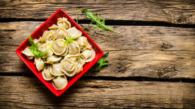 Steamed homemade ravioli with herbs in a Cup. On wooden background. Free space for text . Top view Stock Photo