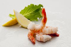 Steamed Jumbo headless shrimps with deli leaves and Lemon on white plate on white background Royalty Free Stock Photo