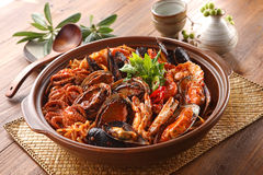 Steamed kimchi seafood with abalone, blue mussel, octopus, crab. And herbs in big bowl on wooden korean table deliciously Royalty Free Stock Photos