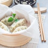 Steamed Korean dumplings Mandu with chicken meat and vegetables. In bamboo steamer, square Stock Photos