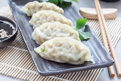 Steamed Korean dumplings Mandu with chicken meat and vegetables. On a black plate, horizontal Stock Images