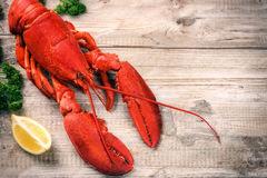 Steamed lobster with lemon on wooden  background Royalty Free Stock Images