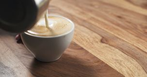 Steamed milk pour into coffee cup to make cappuccino Stock Photo