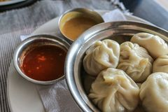 Steamed momos (dumplings) and dipping sauce. Momos are a popular part of Nepalese and Tibetan cuisine. Selective focus Royalty Free Stock Photos