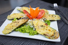 Steamed Mussels baked with cheese. Steamed Mussels baked with cheese on white dish Stock Photography
