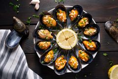 Cooked mussels recipe. Top view. Steamed mussels in white wine sauce with parsley and garlic. Tasty spanish seafood recipe royalty free stock photography