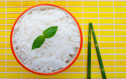 Steamed rice. Bowl of steamed rice on yellow with green bamboo chopsticks Royalty Free Stock Photography