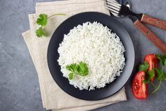 Steamed rice on black plate. Gray stone background. Top view royalty free stock photos
