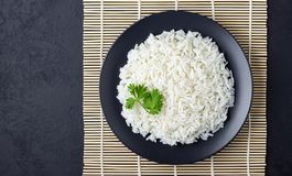 Steamed rice on black plate over bamboo tablecloth. Black stone background. Top view with copy space royalty free stock images