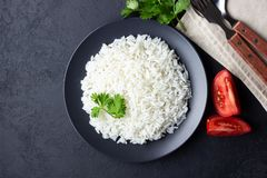 Steamed rice on black plate. Black stone background. Top view stock photography