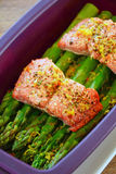 Steamed salmon and asparagus. Fresh wild sockeye salmon and organic asparagus spears cooked in silicone steamer. Vertical format with selective focus Royalty Free Stock Images