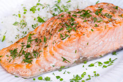 Steamed salmon with fresh herbs and lemon. Rice as a garnish. Royalty Free Stock Photos