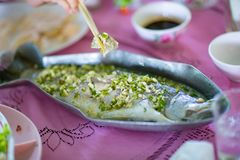 Steamed sea bass fish with lemon, Thai famous local food served on fish shape plate. Thai recommend menu for tourist. Steamed fish with herb and lemon, topped royalty free stock image