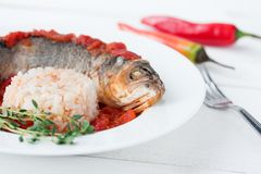 Steamed sea bass in tomato sauce with chili pepper. Stock Photo