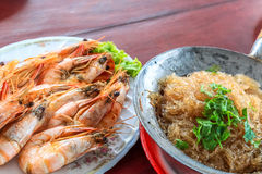 Steamed shrimp/prawn in the white plate and shrimps vermicelli  with glass noodles in hot pot ready to eat. Top view steamed shrimp/prawn in the white plate and Royalty Free Stock Images