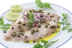 Steamed skate wing with Caper olive oil on blue wooden background Stock Photos