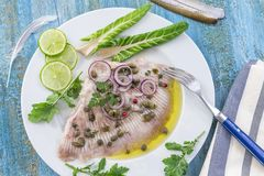 Steamed skate wing with Caper olive oil on blue wooden background Stock Photo