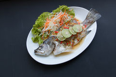 Steamed snapper with lemon on black background. Royalty Free Stock Image