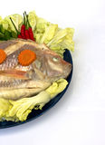 A Steamed Tilapia fish garnish with vegetables Stock Photos