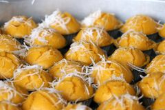 Steamed toddy palm cake in yellow color with white coconut stock photos