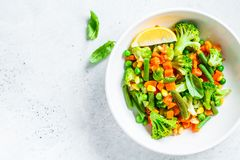 Steamed vegetables broccoli, carrots, beans, peas, corn in white plate, top view. Healthy diet food concept