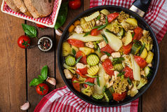 Steamed vegetables with chicken fillet in pan on the wooden background. Royalty Free Stock Photos