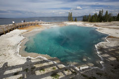Steaming aqua hot spring, with people on boardwalk, Yellowstone. Royalty Free Stock Images