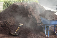 Steaming Bark Dust. Just delivered steaming smoldering hemlock bark dust in a driveway with a wheelbarrow and shovel royalty free stock photo